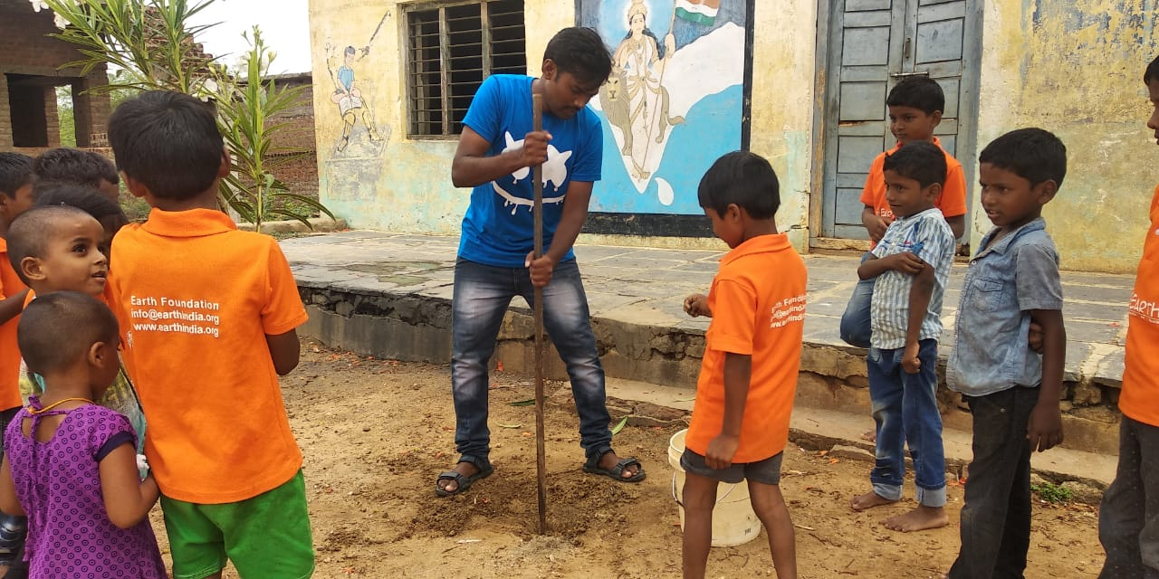 Earth Staff helping kids planing trees